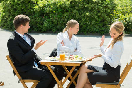 conflicto: Group Of Three Young Businesspeople Having Argument In Restaurant