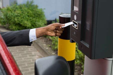 pagando: Persona que se sienta en el coche Usando Aparcamiento Máquina que pagar para aparcar