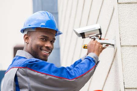 Jonge gelukkig mannelijke Technicus Repareren camera met schroevendraaier