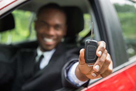 Happy Young African Businessman Sitting In A Car Showing Car Key