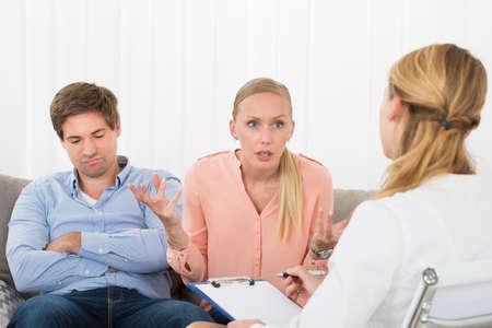 personas enojadas: La mujer enojada sentada con su marido Mujer Consulting Psychologist