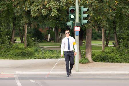 Jonge Blind Man Holding Stick Crossing Road Stockfoto