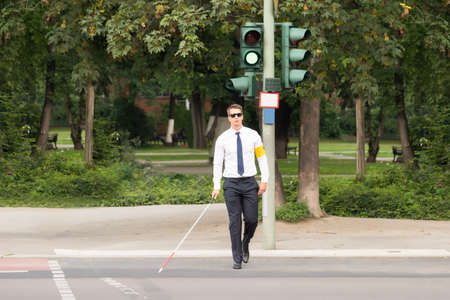 cross ties: Young Blind Man Holding Stick Crossing Road