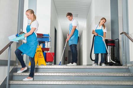 Groupe heureux mâle et femelle Janitor Corridor nettoyage avec des équipements de nettoyage