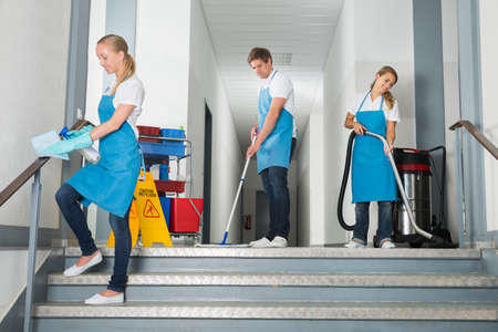 Group Of Happy Male And Female Janitor Cleaning Corridor With Cleaning Equipments Standard-Bild