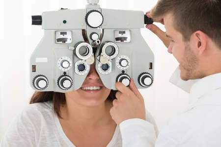 two visions: A Male Ophthalmologist Adjusting The Panel Of Phoropter While Examining Female Patients Eyes Stock Photo