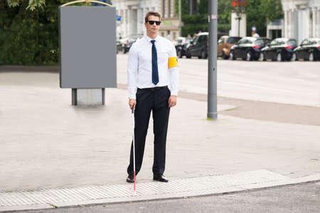 1 person: Blind Man Wearing Armband Standing On Sidewalk