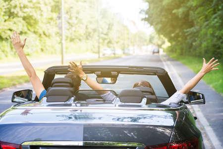 Vista Posteriore Di Una Coppia Seduta In Un Automobile Alzando La Macchina