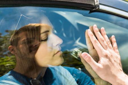 unhappy people: Couple Saying Goodbye Before Car Travel Through The Car Window