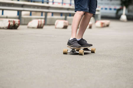 boy skating: Low Section Of Boy Skating On Street Stock Photo