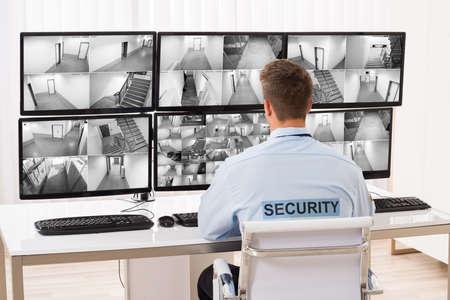 Vista posteriore di un giovane maschio Security Guard monitoraggio di più telecamere a circuito chiuso Footage