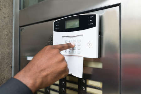 businesspersons: Close-up Of Businesspersons Hand Entering Code In Security System