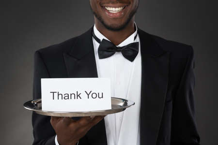 standing up: Close-up Of An African Waiter Holding Thank You Card In Tray