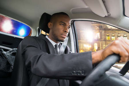 pulled over: Young African Businessman Chased By Police While Driving Car Stock Photo