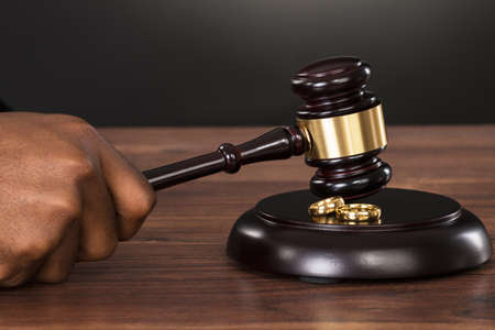 judicial proceeding: Close-up Of A Judge Hands Hitting Gavel With Golden Rings At Desk