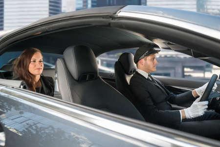 Hermosa mujer joven que viaja en un coche con chófer masculino hermoso Foto de archivo