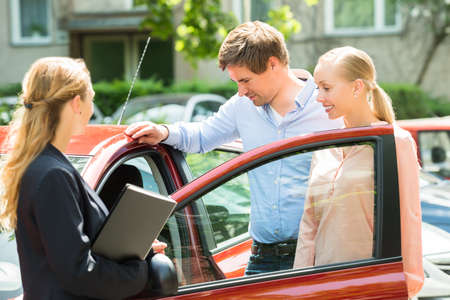 saleswoman: Saleswoman Standing Besides Couple Looking At New Red Car