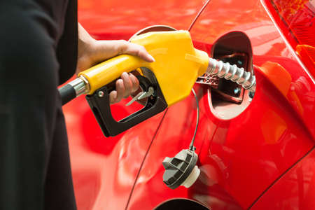 bomba gasolina: Close-up Of Businesswomans Hand Refueling Cars Tank By Holding Petrol Pump Nozzle Foto de archivo