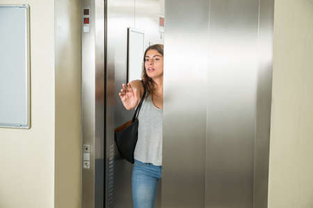 Young Woman Trying To Stop Door In Elevator Фото со стока
