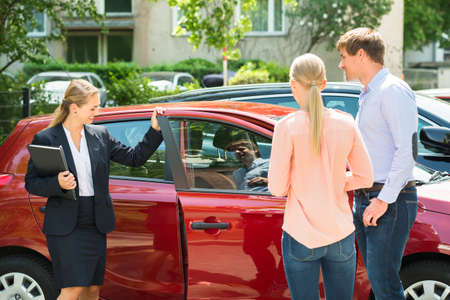 sell car: Happy Female Dealer Showing New Red Car To Young Couple