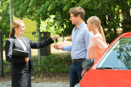sell car: Young Saleswoman Giving Car Key To Happy Couple