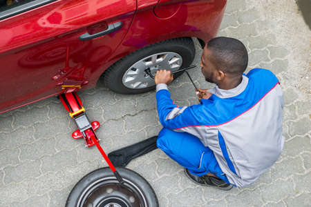 changing: Young African Mechanic Changing Tire Of A Car With Wrench