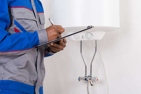 house inspection: Close-up Of Male Plumber Writing On Clipboard