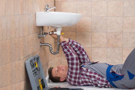 Happy Young Male Plumber Lying On Floor Fixing Sink In Bathroom