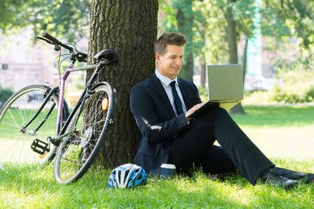 businessman suit: Smiling Young Male Businessman Using Laptop In Park