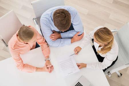 Erhöhte Ansicht des weiblichen Immobilienmaklers Erklären Dokument Um Junges Paar