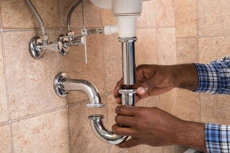 バスルームのシンクを固定男性配管工の手のクローズ アップ 写真素材