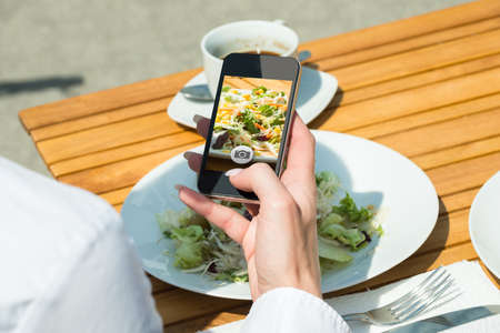 tomando refresco: Close-up Of Persons Hand With Mobile Phone Taking Picture Of Food At Restaurant