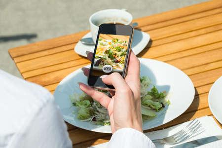 tomando refresco: Primer plano de la mano de la persona con el teléfono móvil que toma el cuadro de comida en el restaurante