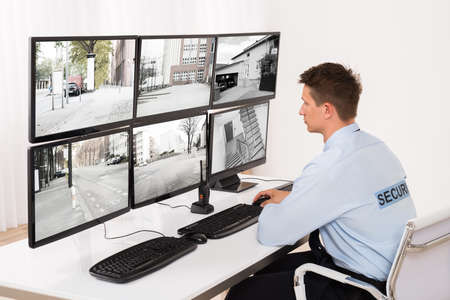 Rear View Of A Young Male Security Guard Monitoring Multiple CCTV Footage Фото со стока - 65163157