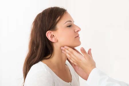 Primer plano de la mano de un doctor toca la garganta de un paciente en la clínica