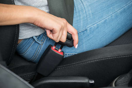 travel woman: Close-up Of Females Hand Sitting Inside Car Fastening Seat Belt Stock Photo