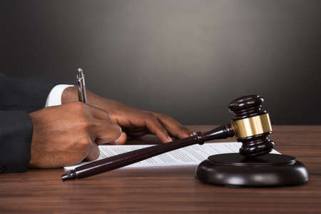 trial indoor: Close-up Of A Judge Writing On Paper With Gavel At Desk Stock Photo