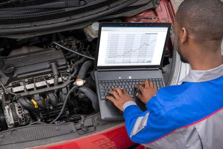 Giovane meccanico maschio usando il computer portatile mentre esamina il motore dell'automobile