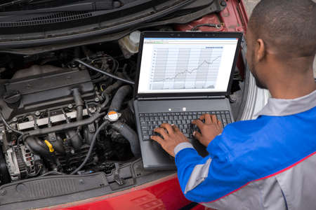 Young Male Mechanic Using Laptop While Examining Car Engine Banco de Imagens