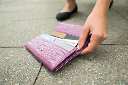 lost: Close-up Of A Woman Picking Up Fallen Wallet On Street