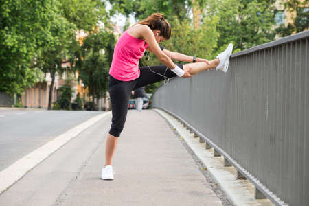 Young Woman Stretching Her Legs Over Fence At Road Stock Photo