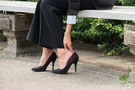 Close-up Of Businesswomans Hand Sitting On Bench Removing High Heels Reklamní fotografie