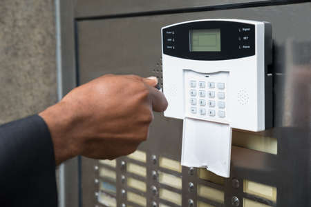 alarm button: Close-up Of Businesspersons Hand Using Remote Control For Operating Door Security System