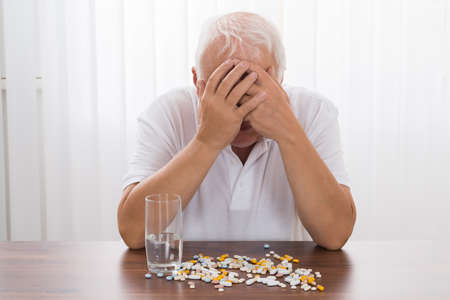 Depressed Senior Man With Pills On Desk Imagens