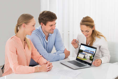 showing: Estate Agent Showing House On Laptop To Smiling Young Couple