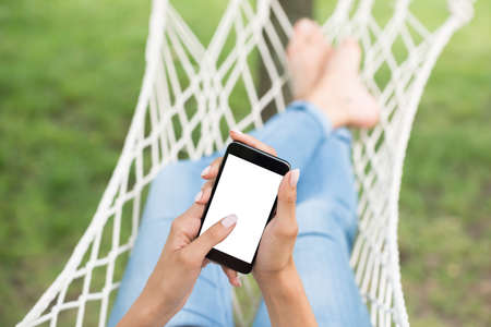 comfortable: Close-up Of Females Hand In Hammock Holding Mobile Phone With Blank Screen