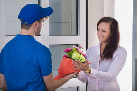 Sonrisa de la mujer joven que recibe el ramo de flores de entrega hombre en el hogar Foto de archivo