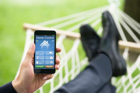 해먹에서 집 컨트롤 시스템을 보여주는 휴대 전화와 남자의 근접
