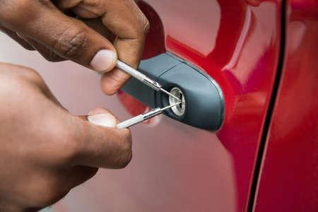 Primer plano mano de la persona de apertura de la puerta del coche con LockPicker Foto de archivo