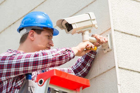 Young Male Technician Installing Camera On Wall With Screwdriver